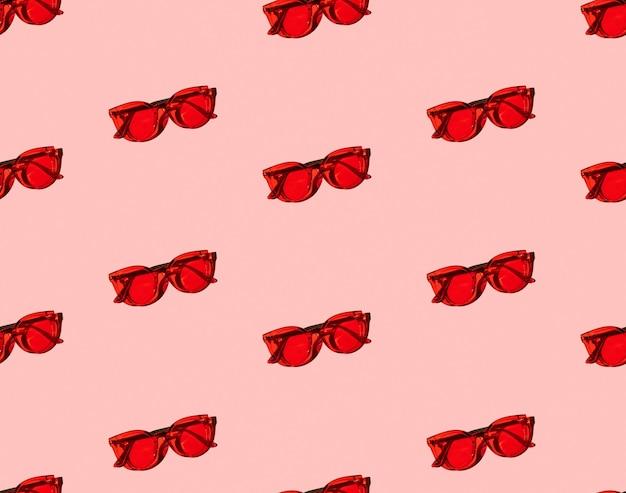 Modèle sans couture avec des lunettes de soleil rouges modernes à la mode sur fond rose