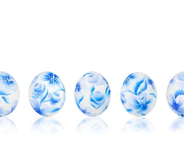 Modèle sans couture d'oeufs de pâques colorés sur fond blanc isolé. oeufs de pâques avec motif floral bleu.