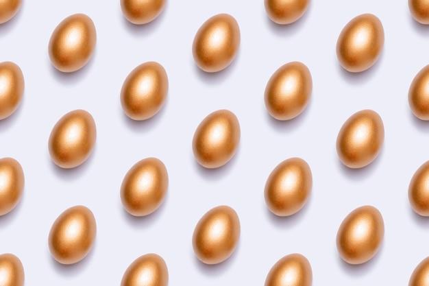Modèle sans couture avec des oeufs de pâques dorés