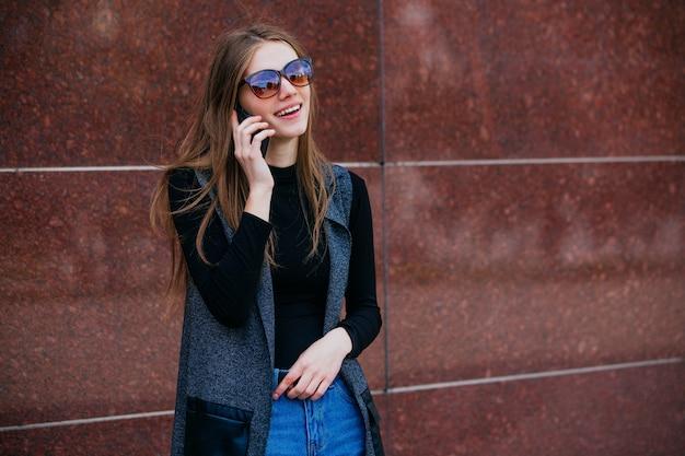 Le modèle se tient contre le mur et parle au téléphone