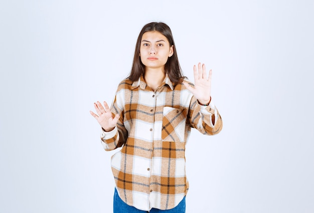 Un modèle sérieux de jeune fille debout et montrant un panneau d'arrêt.