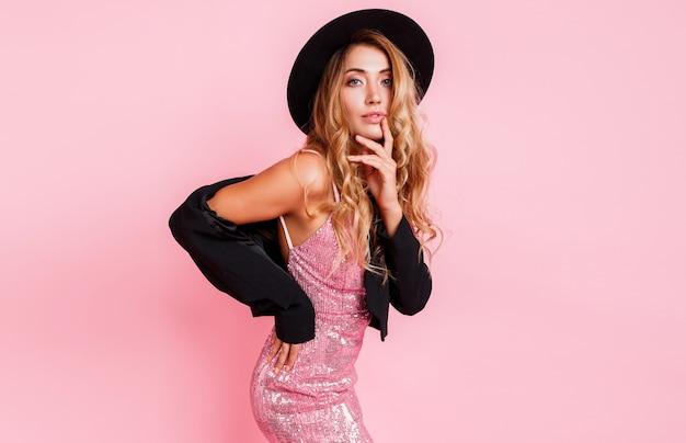Modèle sexy avec des cheveux ondulés brillants parfaits en robe à paillettes de luxe posant sur un mur rose. maquillage naturel. lèvres sexy pleines. chapeau et veste noirs. portrait à la mode.