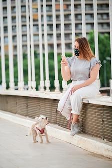 Un modèle sinueux à l'aide de son téléphone portable avec son chien dans une scène urbaine