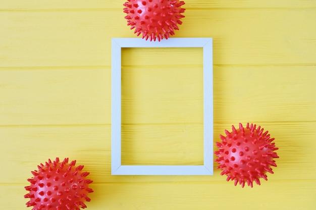 Modèle de souche de virus abstrait boules rouges avec cadre en bois sur fond jaune. syndrome respiratoire