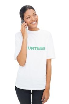 Modèle souriant portant des t-shirts bénévoles ayant un appel téléphonique