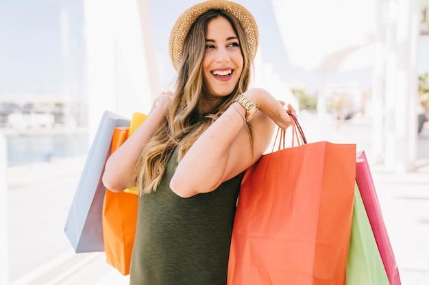 Modèle souriant posant après le shopping