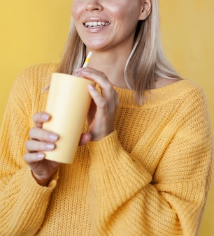Modèle souriant tenant une boisson jaune
