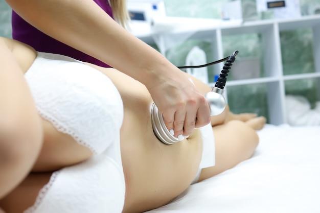 Un modèle en soutien-gorge blanc et culotte blanche est allongé sur la procédure avec un maître de massage, il lui fait un massage par ultrasons, brisant ainsi la cellulite