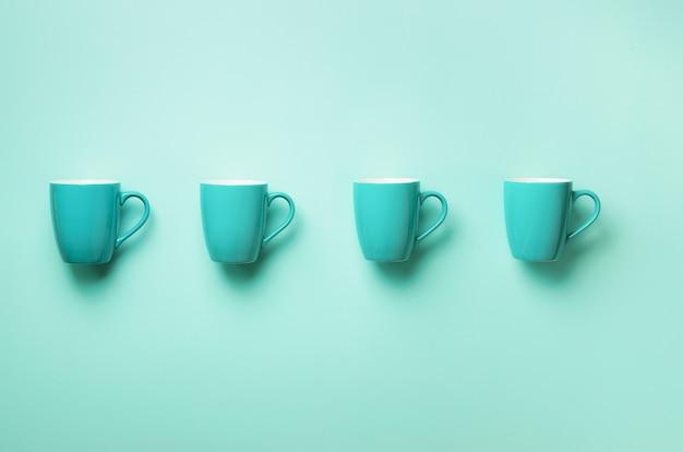 Modèle de tasses bleues sur fond bleu. fête d'anniversaire, concept de fête de naissance. couleurs pastel punchy.