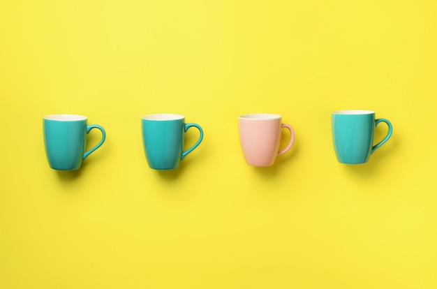 Modèle de tasses bleues et roses sur fond jaune. fête d'anniversaire, concept de fête de naissance.