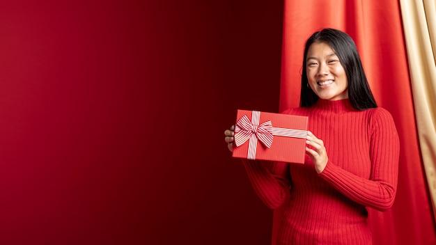 Modèle tenant une boîte-cadeau pour le nouvel an chinois avec espace de copie