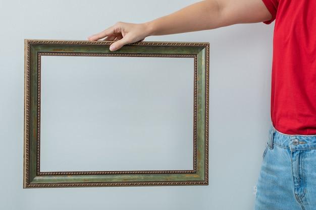 Un modèle tenant un cadre photo métallique
