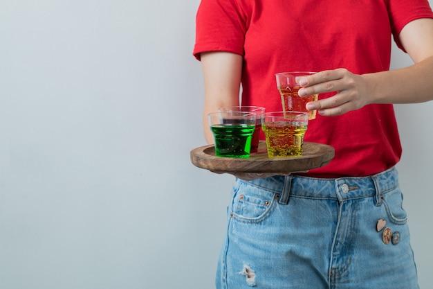 Un modèle tenant un plateau de boissons colorées