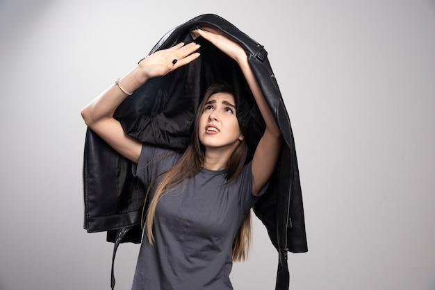 Modèle tenant une veste en cuir noir sur fond gris.