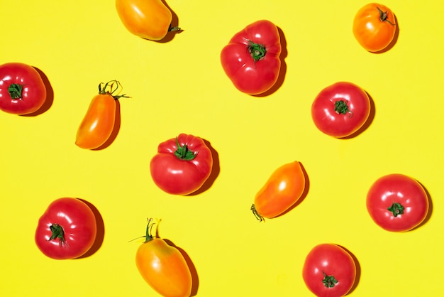 Modèle de tomates jaunes et rouges sur fond jaune