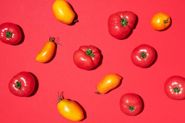 Modèle de tomates jaunes et rouges sur fond rouge