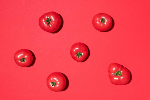 Modèle de tomates rouges sur fond rouge