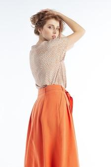 Modèle touchant ses cheveux et posant dans un chemisier léger et une jupe orange