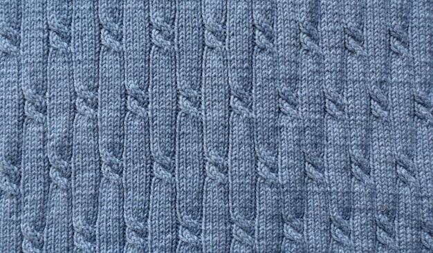 Modèle en tricot. gros plan de la texture de la laine tricotée. maille à motif bleu.