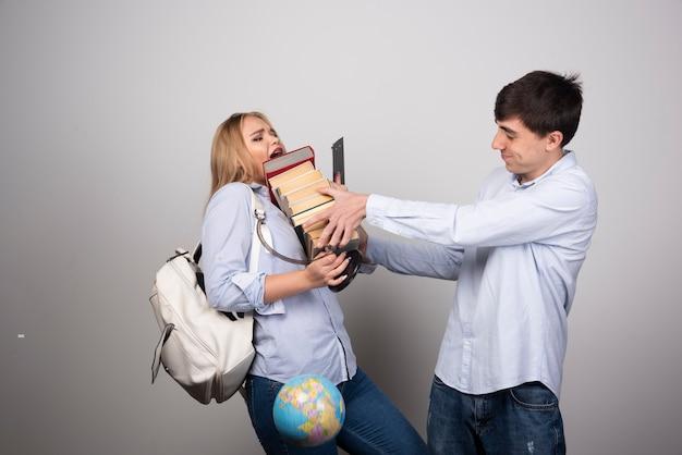 Modèle de type brune donnant une pile de livres à une femme blonde