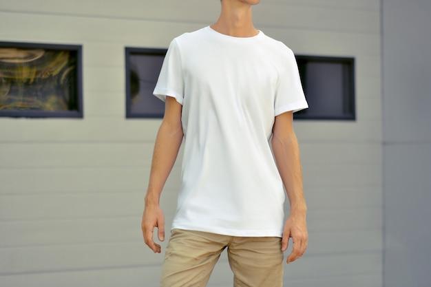 Modèle urbain de vêtements. yong slim guy vêtu d'un t-shirt vierge et d'un short marron se tient près du mur profilé en métal blanc avec des fenêtres noires. la maquette peut être utilisée pour votre conception.