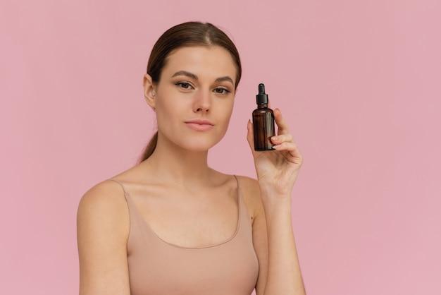 Modèle utilisant un produit cosmétique naturel pour un derme facial hydraté, éclatant et sain. huile essentielle pour la thérapie anti-âge.
