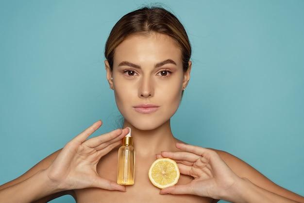 Modèle utilisant un produit cosmétique naturel. sérum à la vitamine c.