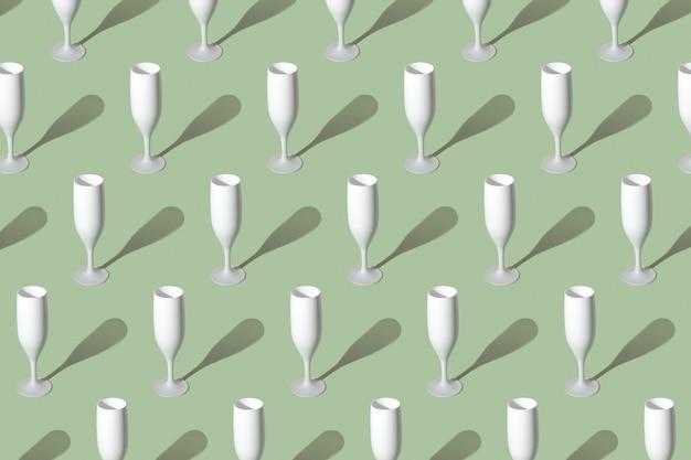 Modèle avec un verre de champagne blanc sur une surface verte.
