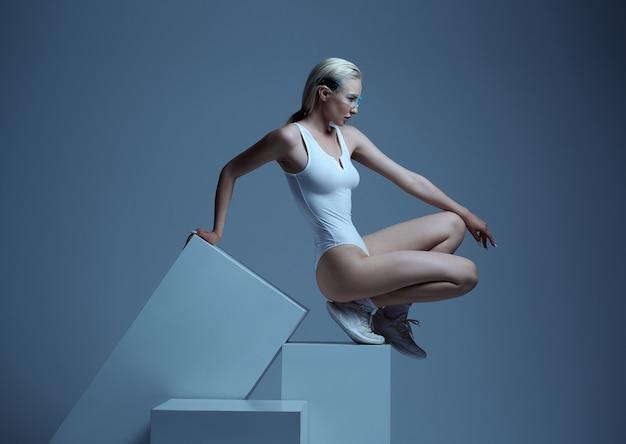 Modèle en vêtements blancs et lunettes futuristes allongées sur des cubes, fond gris clair. personne de sexe féminin dans un style de réalité virtuelle, technologie future