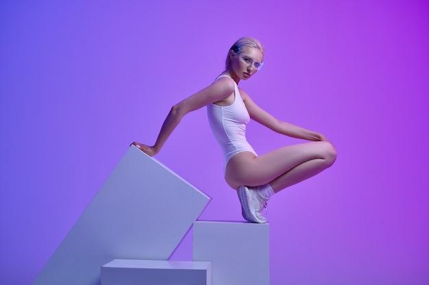 Modèle en vêtements blancs et lunettes futuristes allongées sur des cubes. personne de sexe féminin dans un style de réalité virtuelle, technologie future