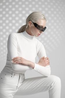 Modèle en vêtements blancs et lunettes futuristes, fond gris clair. personne de sexe féminin dans un style de réalité virtuelle, technologie future, concept de futurisme