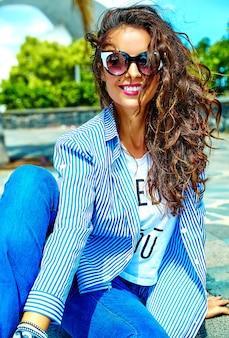 Modèle en vêtements d'été hipster posant dans la rue