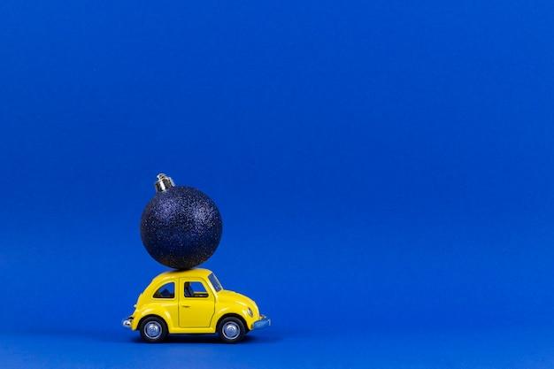 Modèle de voiture jouet rétro jaune avec petite boule de décoration d'arbre de noël bleu marine sur bleu