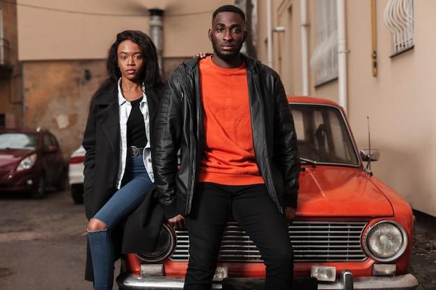 Modèles afro-américains posant sur la voiture