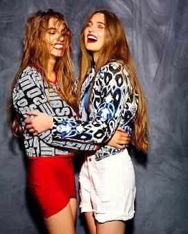 Modèles de belles jeunes femmes souriantes en tissu brillant hipster d'été près du mur gris
