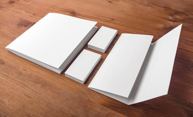 Modèles de cartes de visite, catalogue et livret sur une table en bois. présentation de l'identité d'entreprise