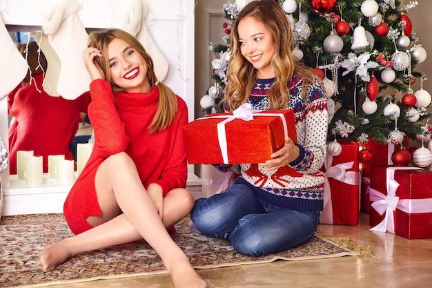 Modèles en chandails d'hiver chauds assis près de l'arbre de noël décoré à la veille du nouvel an.