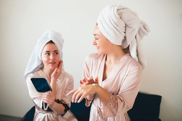 Les modèles féminins appliquent de la crème sur la main et le visage. deux jeunes femmes en serviettes et pyjamas organisent une fête de spa amusante à la maison.