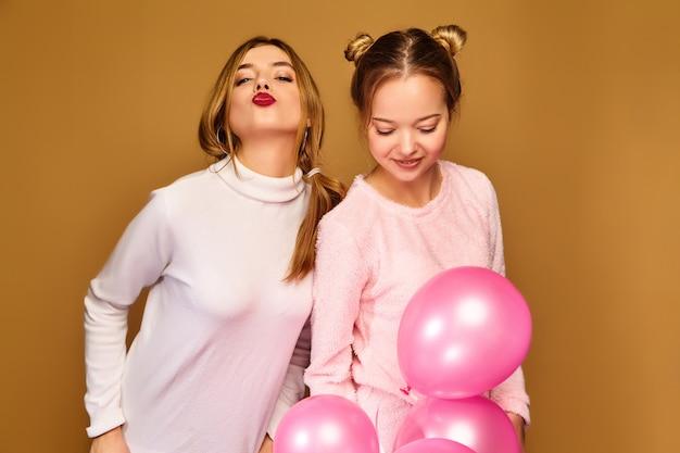 Modèles féminins avec des ballons à air rose sur le mur d'or