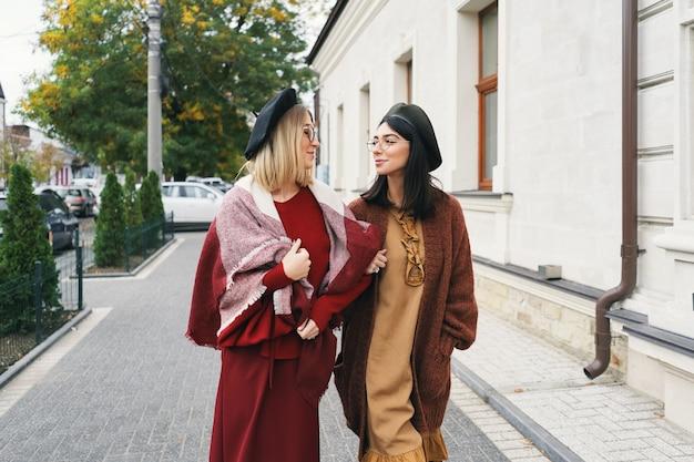 Modèles féminins à la mode sans soucis dans des vêtements et des lunettes d'automne élégants. jeunes filles de la mode dans des vêtements élégants en laine tissée et des chapeaux sur la rue de la ville urbaine, portrait d'automne.