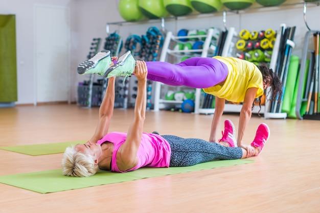 Modèles de fitness féminin faisant des exercices de yoga, l'un allongé sur un tapis de sol, tenant les jambes d'un autre au-dessus d'elle dans un centre sportif