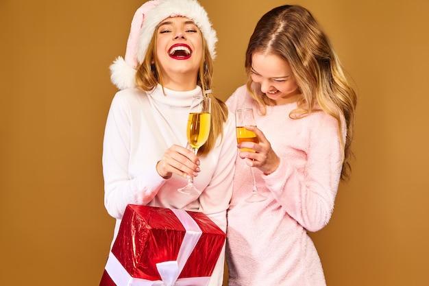 Modèles avec grande boîte-cadeau buvant du champagne dans des verres pour célébrer le nouvel an