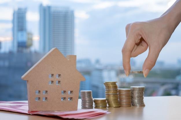 Modèles de maison en bois et main tenant des pièces de monnaie disposées en rangées sur la toile de fond du bâtiment