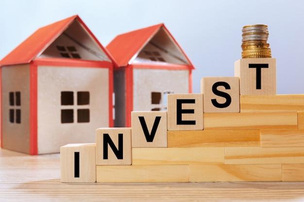 Modèles de maison et inscription sur des cubes en bois - investir. concept d'investissement immobilier.