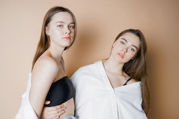 Modèles de mode deux soeurs jumelles belles filles nues regardant la caméra