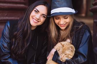Modèles à la mode posant avec chat gingembre