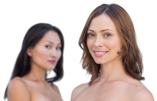 Modèles nus attrayants posant souriant à la caméra