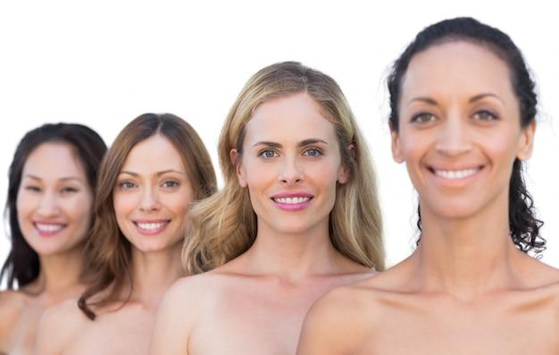 Modèles nus souriants posant dans une ligne en regardant la caméra
