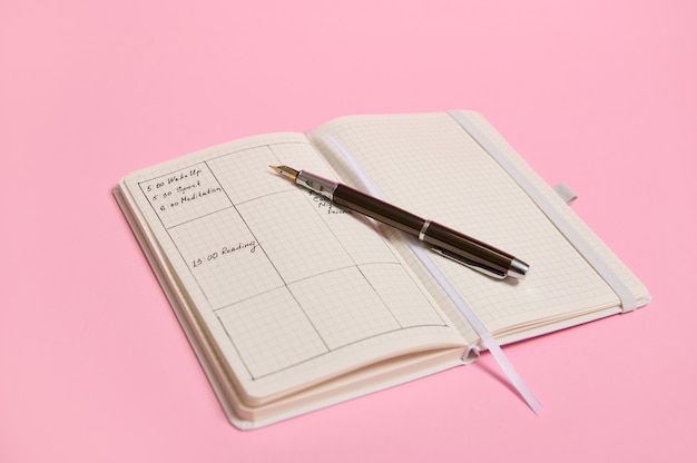 Modèles de planificateur et programme de la journée selon les heures marquées dans le journal et avec un stylo à encre posé sur un cahier ouvert. journal de bord d'affaires, plans d'organisateur de bureau. fond rose, espace copie