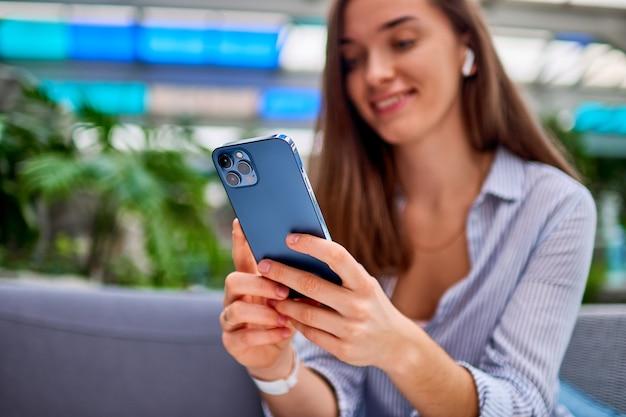 Modern happy attractive casual smiling smart millénaire femme portant des écouteurs sans fil à l'aide de téléphone pour la navigation en ligne et le chat